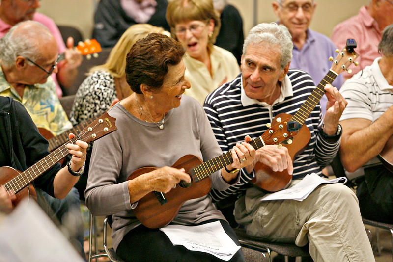 """011414 - DELRAY BEACH  - Tavit Smith, a retired Delray Beach psychotherapist and ukulele player held his first Ukulele Get-Together, for players of all abilities on Jan. 14 at the Delray Beach Public Library. Delray Beach residents Roz and Bob Papell share a laugh during the Delray Beach Public Library  """"Ukulele Get-Together"""".  Photo by Tim Stepien/The Coastal Star"""