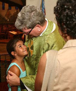"061413 - DELRAY BEACH - After his last mass, The Rev. William ""Chip"" Stokes of St. Paul 's Episcopal Church  is given a warm goodbye by 8-year-old Carrie Connell, who met him as a student while attending  St. Paul's Day School.  ""Chip"" Stokes will be ordained as Bishop of The Diocese of New Jersey on Nov. 2.  Photo by Tim Stepien"
