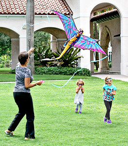 072113 - Inez Layne flies a dragon kite with her daughters Rhyan Fleisher, 5, and Elle Fleisher, 3, during family fun day at The Cornell Museum in Delray Beach.  Photo by Tim Stepien