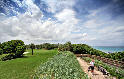 072513 - BOCA RATON - John Granath, Boca resident, walks toward the 8th tee at the Red Reef Executive Golf Course. Pictured at bottom left is the flag for hole 7.  photo by Tim Stepien