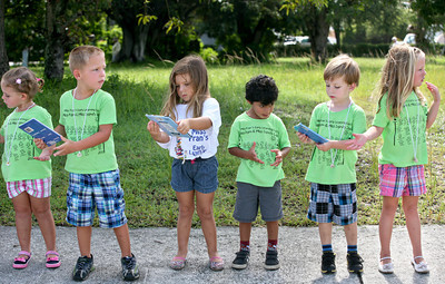 062013 - BOCA RATON - On Thursday morning, more than 300 people showed up to move Boca Raton's old Downtown Library's last 100 books person by person into the new library. The group formed a human chain that spanned the two-block distance between the old library's front door and the new one. Pictured are children from the Miss Fran's Early Learning Center in BocaRaton taking part in the book brigade.  Photo by Tim Stepien
