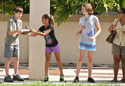 062013 - BOCA RATON - On Thursday morning, more than 300 people showed up to move Boca Raton's old Downtown Library's last 100 books person by person into the new library. The group formed a human chain that spanned the two-block distance between the old library's front door and the new one. Pictured is one of the books that has a video camera attached to it to capture the event. Photo by Tim Stepien