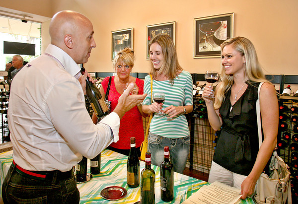 "061313 - DELRAY BEACH -  Once ""Old Vines"",  the wine shop at 900 Atlantic Ave. in Delray Beach became ""The Wine Wave"" on June 5. At left, Fabio De Filippi, owner/CEO Tuscany Distributors Palm Beach discusses the different wines with Anne M. Ennis, VP/Branch Manager Paradise Bank, Delray Beach.  Photo by Tim Stepien"