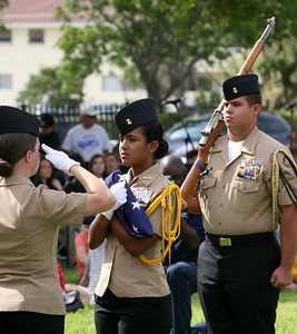 052713 - BOCA RATON - Boca Raton Community High School Navy Junior ROTC Cadet Commander Jaymarie Colon-Perez, center, is saluted while carrying the flag during a Memorial Day Observance Monday morning at the Boca Raton City cemetery.  Participating groups included American Legion Post #277 and its auxiliary unit, Boca Raton Elks Lodge #2166, Boca Raton Community High School unit of the Navy Junior ROTC under the direction of Commander Ken Bingham, Boca Raton Community High School Band under the direction of Jenn Mimmino, Fort Lauderdale Highlanders, and honor guard units representing the City's Police Services and Fire/Rescue Services..  Photo by Tim Stepien