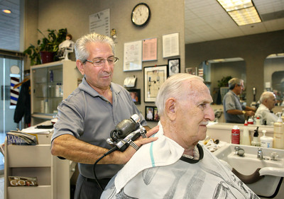051513 - BOCA RATON - Pat Grego, a barber at Mr Vito Men's Hair Designers, gives a shoulder massage to Boca resident Jerry Martin.  The massager he is using is an antique Oster from the 1970's. Mr Vito Men's Hair Designers was established in 1972,