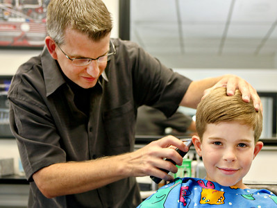 051113 - DELRAY BEACH - Jake Julien, 7, a student at Gulf Steam School and resident of the town of Gulf Stream, gets his hair cut at the  5th Ave. Barbershop in Delray Beach by Brad The Barber.  Jake was getting his hair cut with his Brother Miles Julien, 4, and his father Bobby Julien.  Photo by Tim Stepien