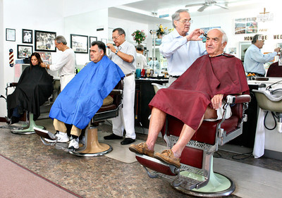 "051513 - OCEAN RIDGE - Lino Marmorato, pictured center, the owner of Colby Barber Shop in Ocean Ridge, cuts the hair of Boynton resident Joe Giuliano. Pictured at right, Paul Hansen cuts the hair of Hypoluxo resident Ken Keller.  Pictured back left, ""Fonzi"" Palmieri cuts the hair of Delray resident Alexandra Pena. The barbershop was in full swing Wednesday morning.  Photo by Tim Stepien"