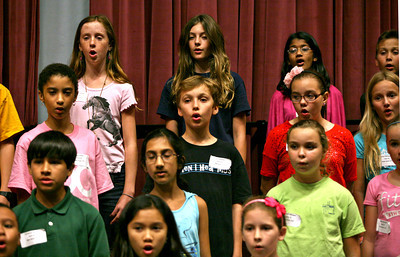 "051313 - WPB - Blake Dykstra, center, sings during rehearsal Monday evening. Blake and his brother Devin are just two of the more than 350 most talented voices in the area spanning ages 8 – 18 who performed on the main stage of the Kravis Center with Palm Beach County's award winning community chorus on May 19th for the organization's 10th Anniversary performance, ""Ubuntu."" Photo by Tim Stepien"