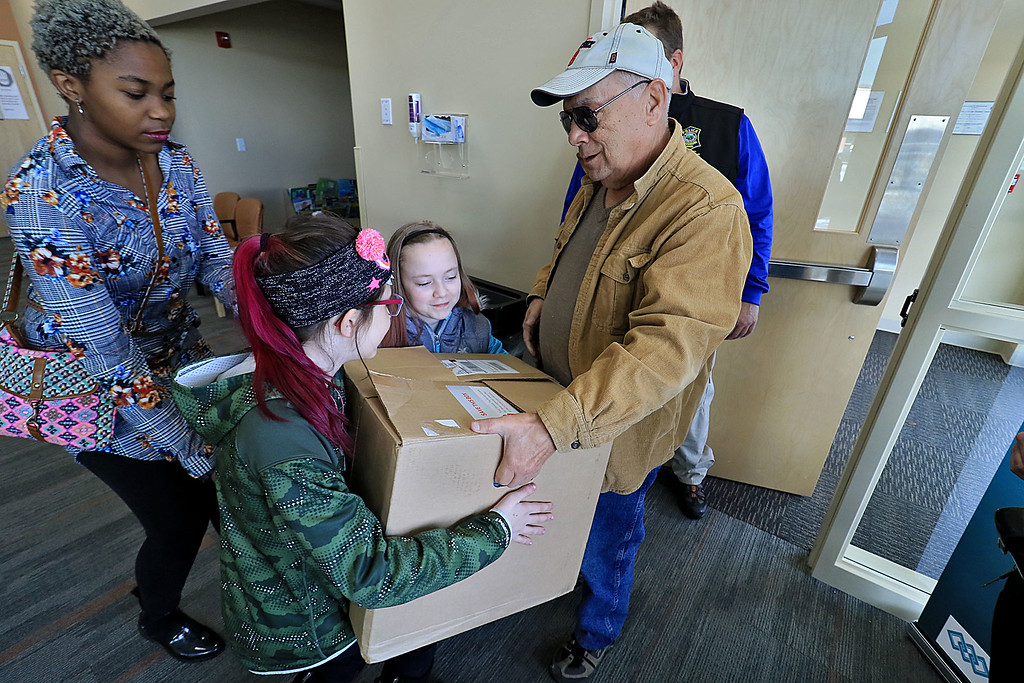 . The Fitchburg Police Department held a coat drive at Community Health Connections on Saturday morning, November 17, 2018. Girl Scout Troop 30713 was on hand to help fold and organize all of the clothes they got donated. Girl Scouts Riley Baker, 12, Alexiss Austin, 13, and Kayleigh LeFrancois, 12, except a box of clothes from Fred Robichaud of Fitchburg during the drive. SENTINEL & ENTERPRISE/JOHN LOVE