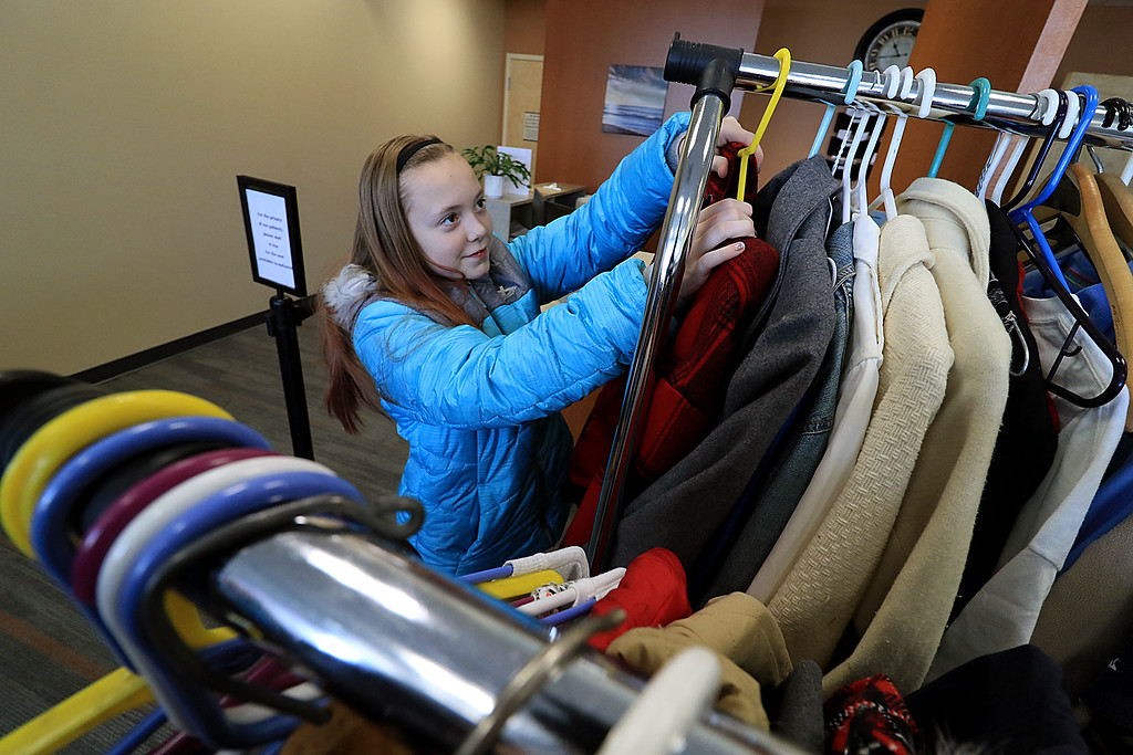 . The Fitchburg Police Department held a coat drive at Community Health Connections on Saturday morning, November 17, 2018. Girl Scout Troop 30713 was on hand to help fold and organize all of the clothes they got donated. Girl Scout Kayleigh LeFrancois, 12, organizes  some coats they got at the drive. SENTINEL & ENTERPRISE/JOHN LOVE