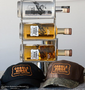 The finished product along with some hats bearing the company logo are seen during a tour of the Cobble Ridge Distillery in Bangor, Calif. Thurs. Sept. 29, 2016. (Bill Husa -- Enterprise-Record)