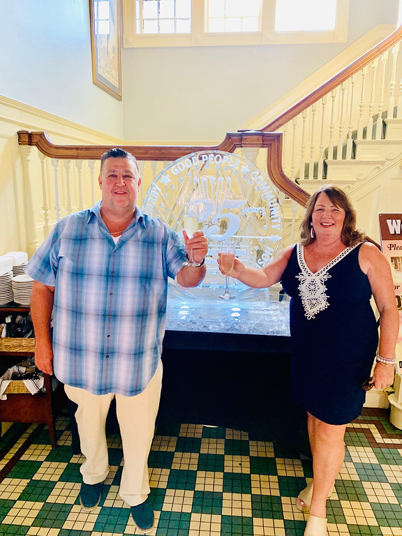 . The dynamic duo, Scott and Kathy Plath of Lowell, owners of Cobblestones and Moonstones, cheer their loyal patrons in front of a giant ice sculpture made by Incredible Ice of Lawrence.