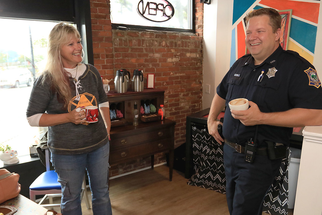 """. Wednesday was \""""Coffee with a Cop\"""" and in Fitchburg they held their event at Strong Style Coffee on Cushing Street. Patrolman James Farrell chats with Brenda Coveno-Watson of Fitchburg during the event. SENTINEL & ENTERPRISE/JOHN LOVE"""