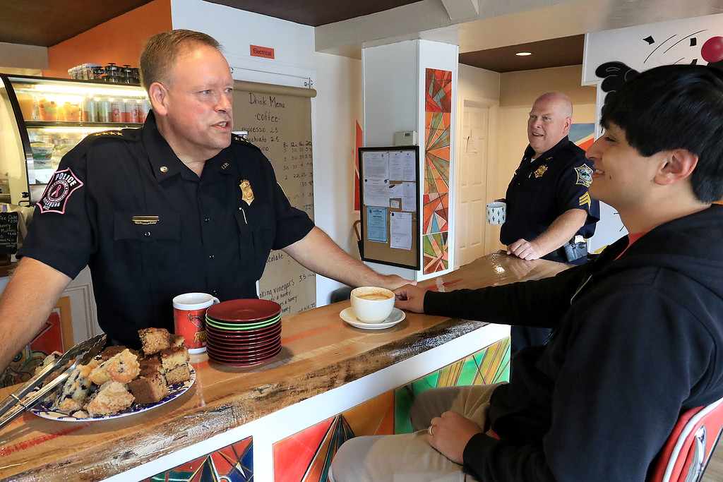 """. Wednesday was \""""Coffee with a Cop\"""" and in Fitchburg they held their event at Strong Style Coffee on Cushing Street. Fitchburg Police Chief Ernest Martineau chats with Adrian Gates of Fitchburg during the event. SENTINEL & ENTERPRISE/JOHN LOVE"""