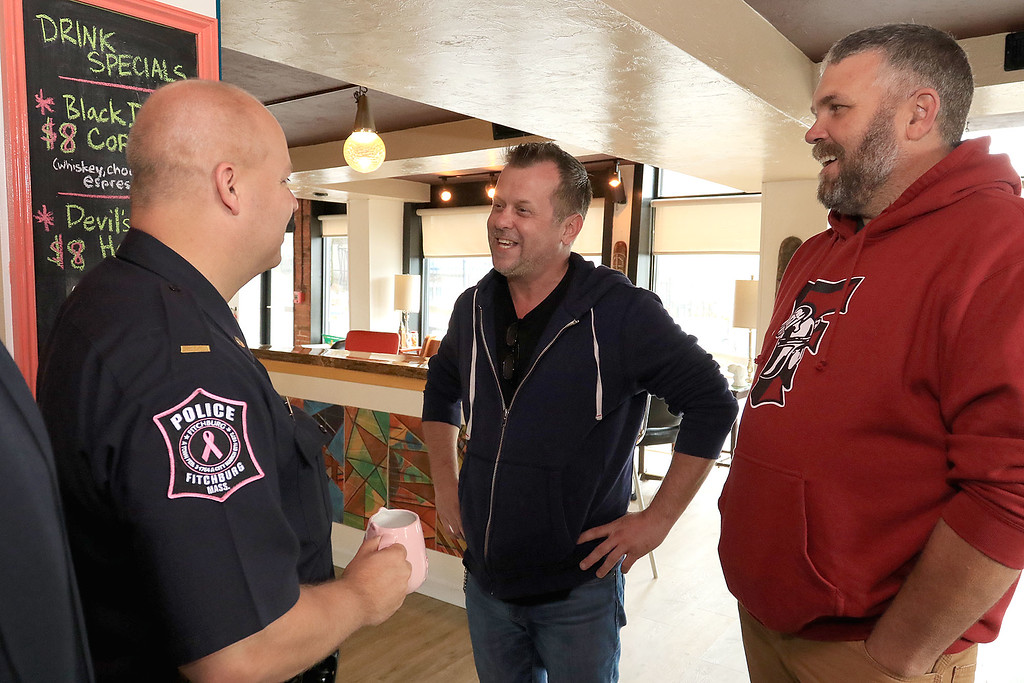 """. Wednesday was \""""Coffee with a Cop\"""" and in Fitchburg they held their event at Strong Style Coffee on Cushing Street. During the event Robert Leger, center, and Scott Reilly ran into their friend Lt. Jeffrey Howe during the event they all grew up in Fitchburg together but Leger now lives in Los Angeles California and Reilly now lives in North Carolina. They had fun catching up. SENTINEL & ENTERPRISE/JOHN LOVE"""