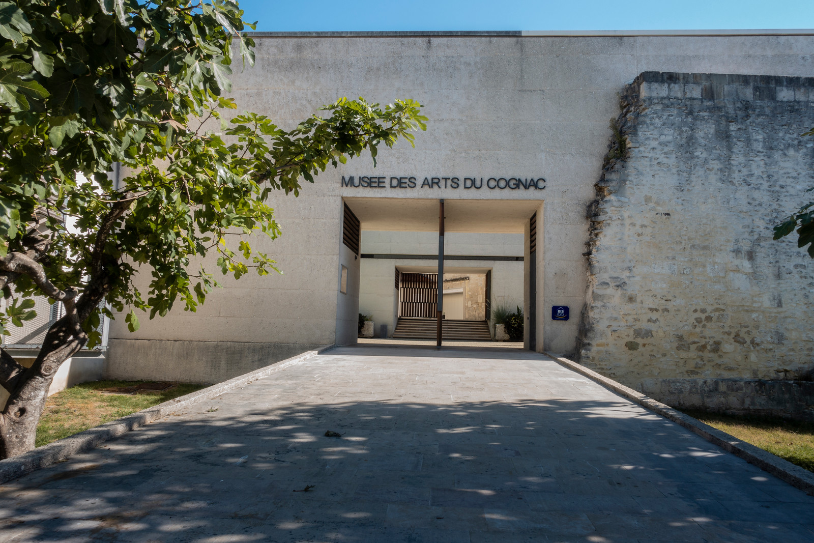 Sunny entrance into the museum of Cognac shaded by green trees