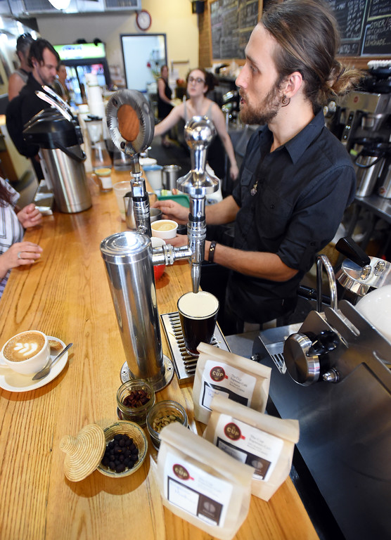 . Ethan Martin pours a nitro draft coffee and helps customers  at The Cup in Boulder on Friday.  Cliff Grassmick  Staff Photographer July 28, 2017