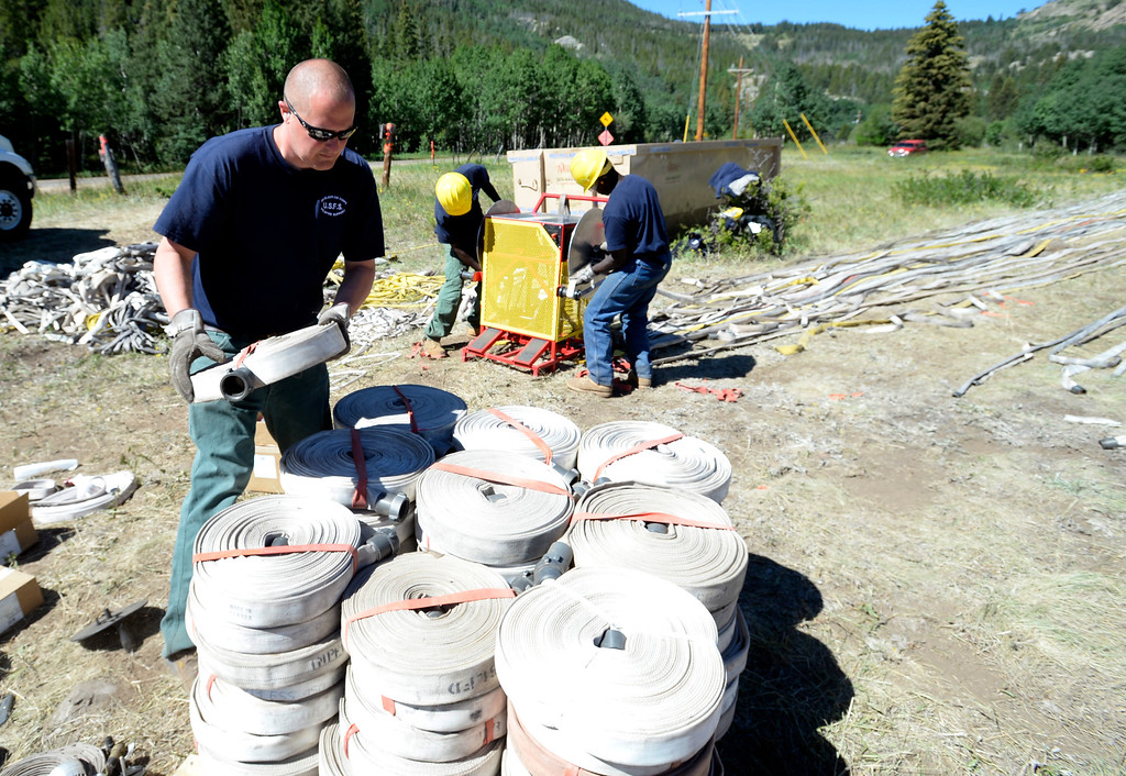. Chad Bentz,  of Boxeleder Job Corps. of Nemo, S.D., stacks up fire hoses used to fight the Cold Springs Fire. Fire and support crews from around the western US are wrapping up operations at the Cold Springs Fire outside Nederland on Thursday, July 14, 2016.For more photos and a video, go to www.dailycamera.com. Cliff Grassmick  Staff Photographer  July 14, 2016