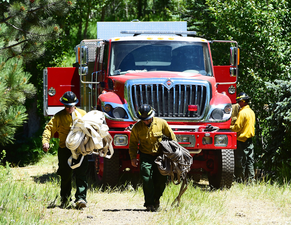 . Firefighters walk out of a burn area near Cold Springs Rd and the Peak to Peak Highway on Thursday. For more photos and a video, go to www.dailycamera.com. Cliff Grassmick  Staff Photographer  July 14, 2016