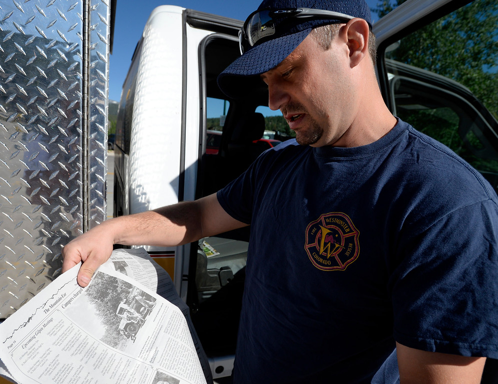 . Nathan Olson,  of  Westminster Fire/Rescue, shows a photo of the fire starter suspects in the local Nederland newspaper. For more photos and a video, go to www.dailycamera.com. Cliff Grassmick  Staff Photographer  July 14, 2016