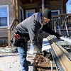 The cold weather did not stop work that had to be done on a house on South street in Fitchburg on Friday, January 11, 2019. Working on bending some aluminum siding to go around the new windows on the house is Dennis Allain with Austin Paint Company.  SENTINEL & ENTERPRISE/JOHN LOVE