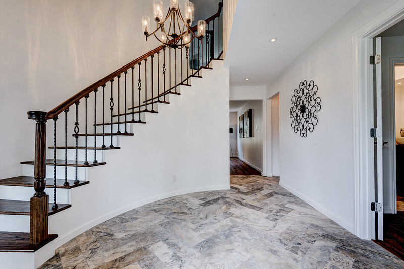Stunning entry featuring a beautiful curved staircase with stained oak stair treads and ornate wrought iron highlighted by the herringbone travertine floor and heavy nine light iron chandelier.