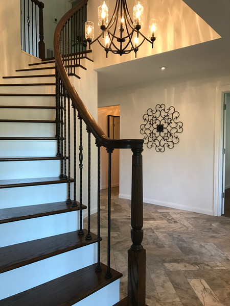 Stunning entry featuring a beautiful curved staircase with hand finished oak stair treads, original handrail and ornate wrought iron balusters highlighted by a beautiful herringbone travertine floor and heavy nine light iron chandelier.