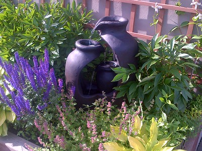 Water feature among Catmint, Salvia, Hostas, Peonies and Gazelle clematis
