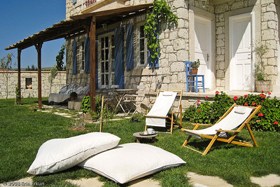 Alaçat Kırevi - Comfortable chairs and pillows on the grass invite visitors to take a snooze in the sun.