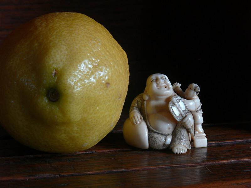 laughing Budha and lemon on teak