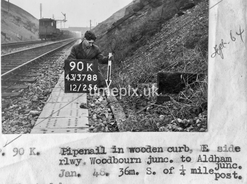 SK378890K, Man marking Ordnance Survey minor control revision point with an arrow in 1940s Sheffield