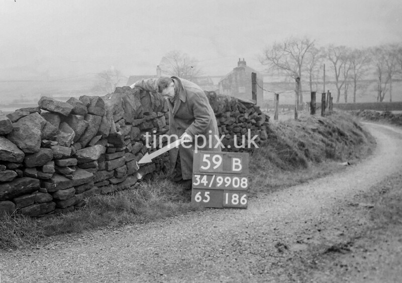 SD990859B1, Man marking Ordnance Survey minor control revision point with an arrow in 1950s