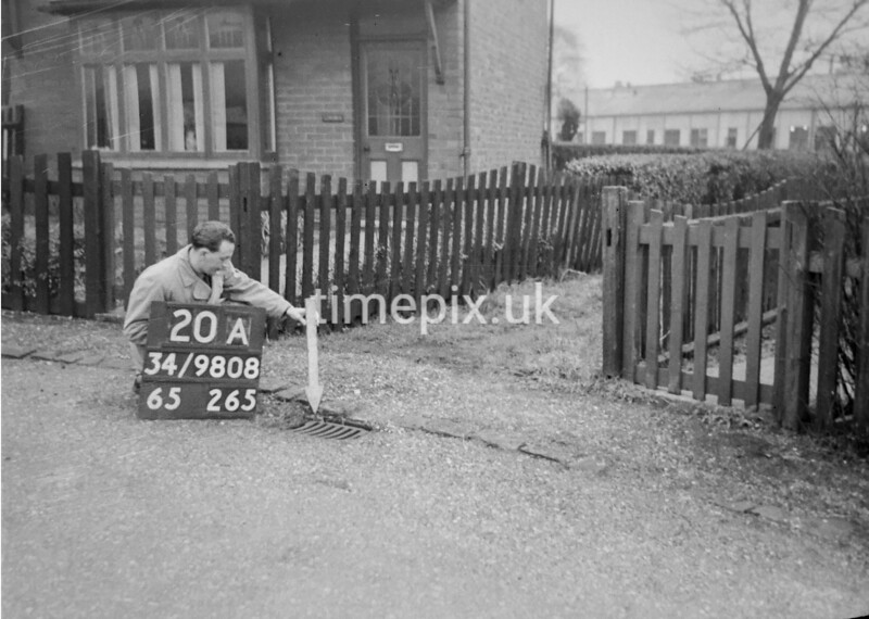 SD980820A, Man marking Ordnance Survey minor control revision point with an arrow in 1950s