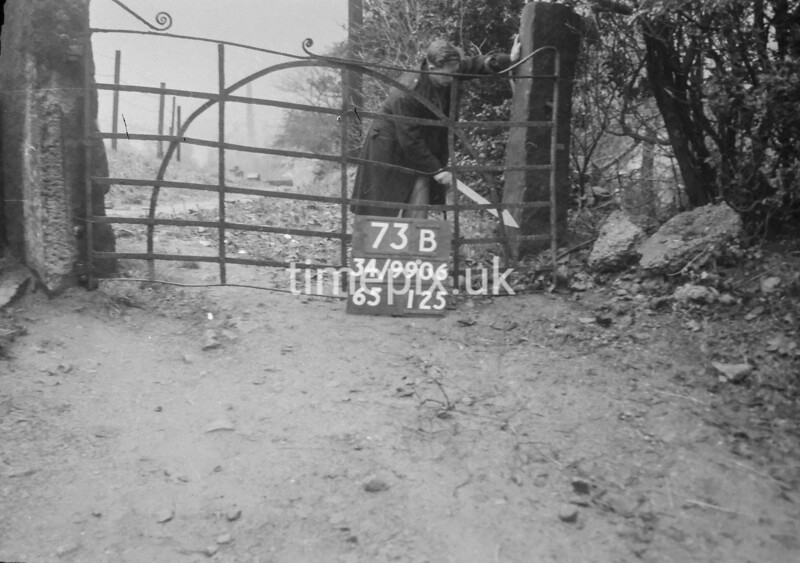 SD990673B, Man marking Ordnance Survey minor control revision point with an arrow in 1950s