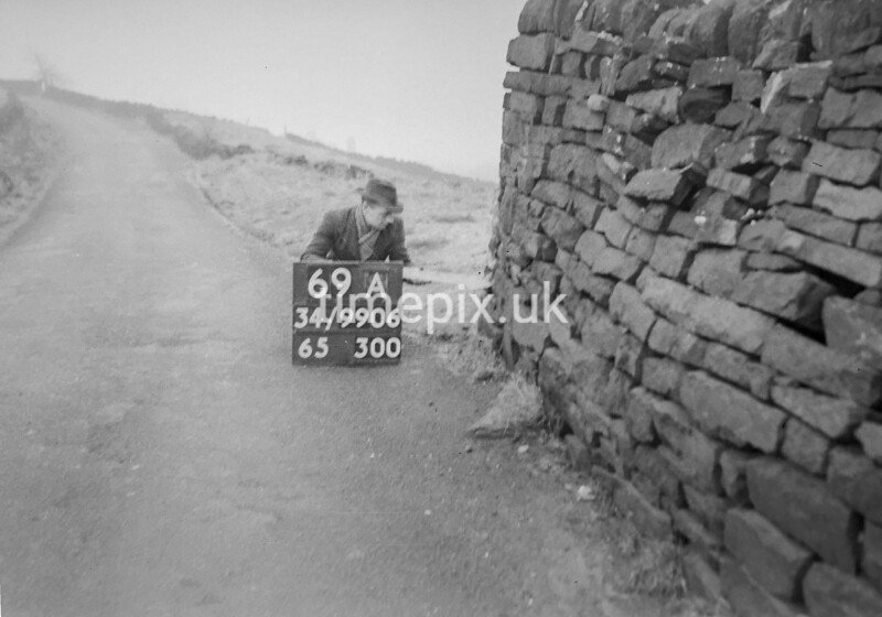 SD990669A, Man marking Ordnance Survey minor control revision point with an arrow in 1950s