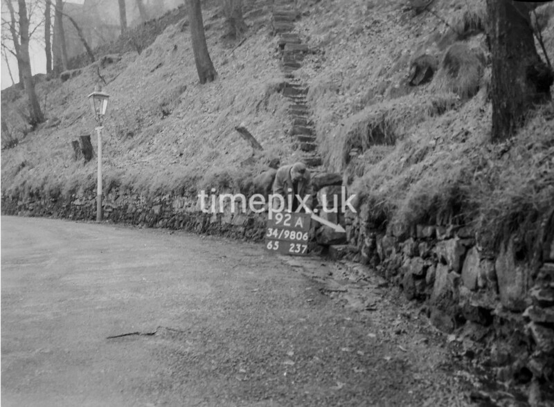 SD980692A, Man marking Ordnance Survey minor control revision point with an arrow in 1950s