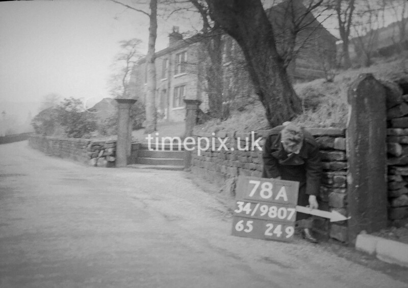 SD980778A, Man marking Ordnance Survey minor control revision point with an arrow in 1950s