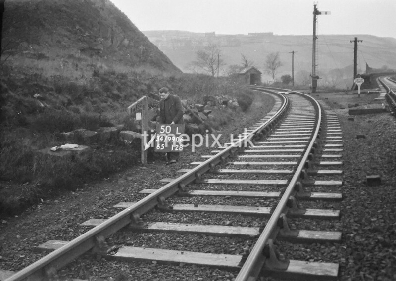 SD990650L, Man marking Ordnance Survey minor control revision point with an arrow in 1950s
