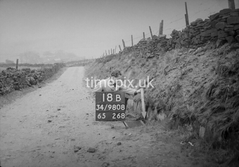 SD980818B, Man marking Ordnance Survey minor control revision point with an arrow in 1950s