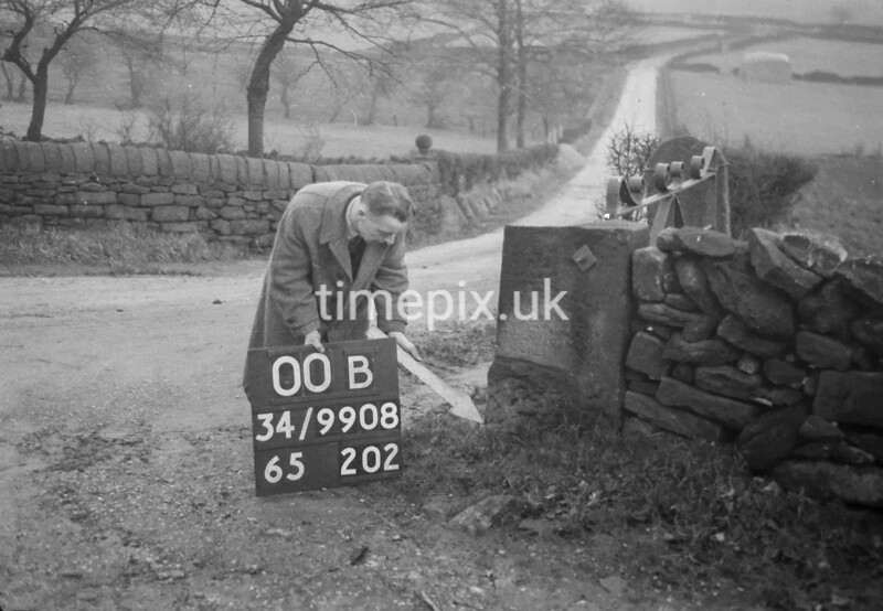 SD990800B, Man marking Ordnance Survey minor control revision point with an arrow in 1950s