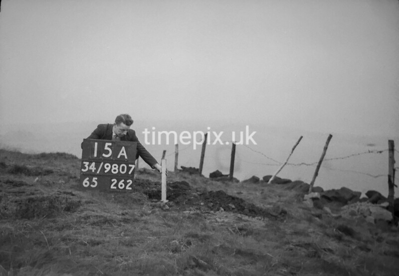 SD980715A, Man marking Ordnance Survey minor control revision point with an arrow in 1950s