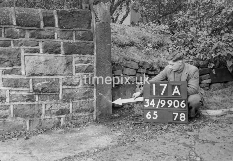 SD990617A, Man marking Ordnance Survey minor control revision point with an arrow in 1950s