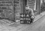 SD990661A, Man marking Ordnance Survey minor control revision point with an arrow in 1950s