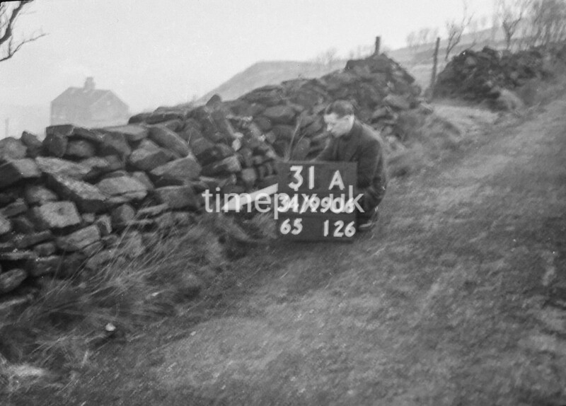 SD990631A, Man marking Ordnance Survey minor control revision point with an arrow in 1950s