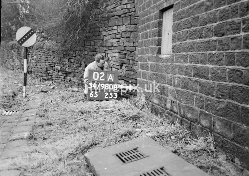 SD980802A, Man marking Ordnance Survey minor control revision point with an arrow in 1950s