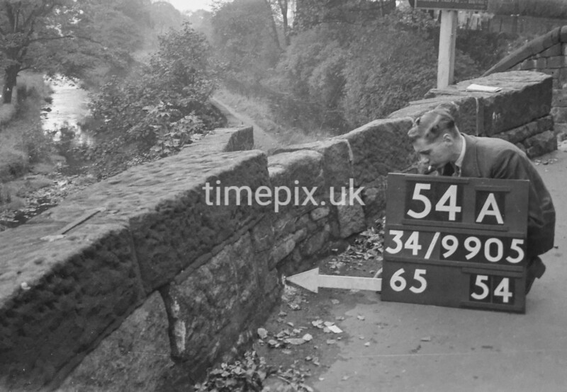 SD990554A, Man marking Ordnance Survey minor control revision point with an arrow in 1950s