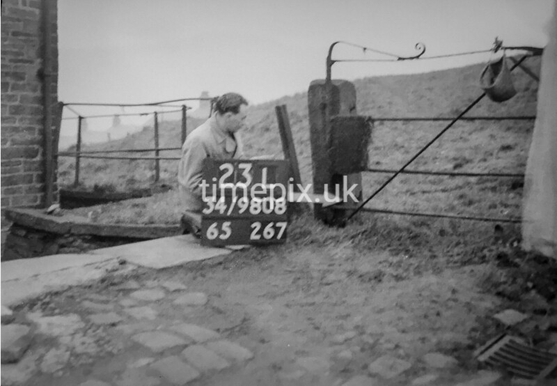 SD980823L, Man marking Ordnance Survey minor control revision point with an arrow in 1950s