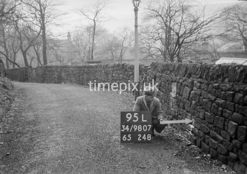SD980795L, Man marking Ordnance Survey minor control revision point with an arrow in 1950s