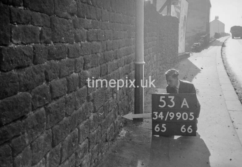 SD990553A, Man marking Ordnance Survey minor control revision point with an arrow in 1950s
