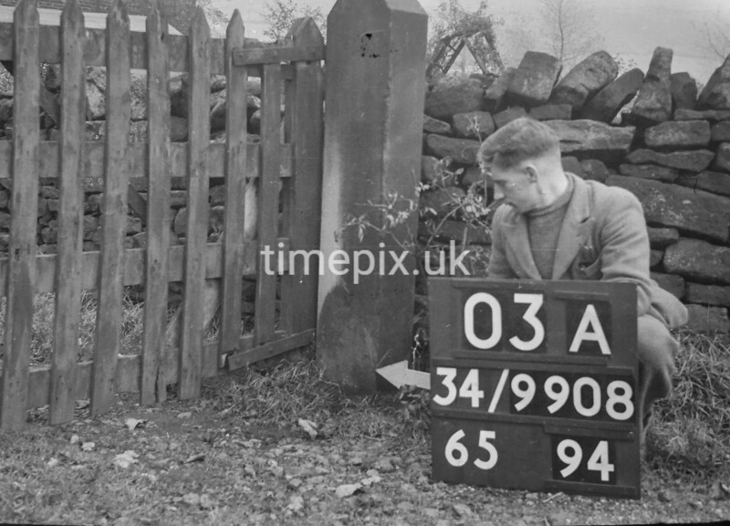 SD980803A, Man marking Ordnance Survey minor control revision point with an arrow in 1950s